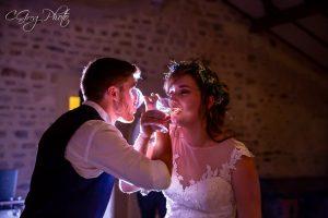 Couple de mariés face à face à boire une coupe de champagne bras croisés